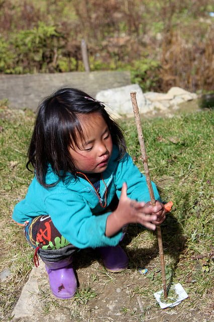 "This image of a little girl in Bhutan twirling a stick is the best image I could find on Flickr while searching for ""happiness engineer."" It works, kinda."